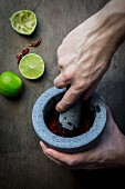 Man s hand with mortar and pestle preparing seasoning paste