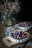 Berry tartetelets with icing sugar in baking dishes on wooden plates with bouquet of flowers in background