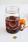 Homemade rum punch with clementines, raisins, cinnamon and lemon zest in a glass jar