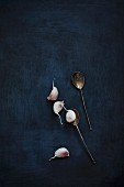 Garlic cloves and vintage silver spoons on a black background