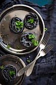 Black ribbon noodles and parsley on a stainless steel plate