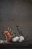 Stacked copper cups and white hen's eggs on wooden table