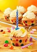 Geburtstags-Cupcake mit Kerze und bunten Geleebonbons