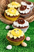 Easter animal themed cupcakes on grass and in a basket with mini easter eggs