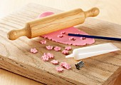Pink icing rolled out on a board with rolling pin, showing a metal flower cutter and white icing tube