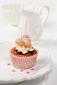 A sweet heart cupcake on a white plate with white milk jug and sugar basin in background
