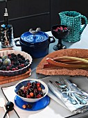 Cherries in a bowl, berries and figs in tart, rhubarb, crockery and cutlery
