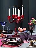 Geschirr, Kerzenleuchter, Obst, Wein und Kaffee auf Tisch
