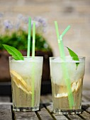 Two glasses of lemonade with mint and straws