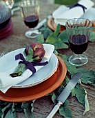 Purple globe artichoke on white serviette and orange plate on wooden table with large artichoke leaves and glasses of red wine