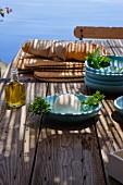 Rustikaler Holztisch am Meer mit blauen Tellern, Brot, Käse und Olivenöl