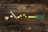 Leek cut into pieces with a knife on a wooden surface