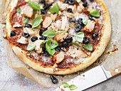Pizza topped with tuna and olives