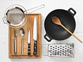 Various kitchen utensils: wok, grater, strainer, vegetable peeler, knives