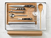 Various kitchen utensils: baking tray, knife, peeler, meat fork, baking paper