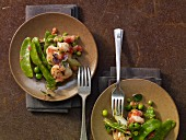 Prawns with sugar snaps, peas and tomatoes