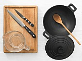 Various kitchen utensils: wok, cooking spoon, knife, measuring cup