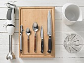 Various kitchen utensils: blender, peeler, spoons, knives, mixing jug, measuring cup
