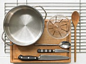 Various kitchen utensils: pot, measuring cup, knives, spoon