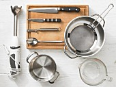 Various kitchen utensils: blender, pots, a measuring cup, strainer, cutlery