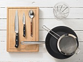 Various kitchen utensils: pan, sieve, measuring cup, knives, spoon