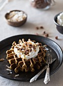 Spicy Pumpkin Waffles with Coconut Whipped Cream served on a dark color plate