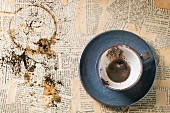 Blue ceramic cup of coffee grounds over old newspaper