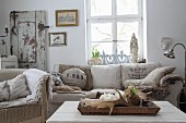 Tablett mit Geweihen vor dem Sofa mit Kissen aus alten Mehlsäcken
