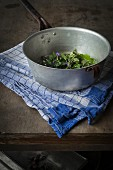 Wild herbs in vintage colander on wooden table