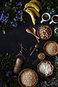 Ingredients for Banana Bread Granola on a dark surface, surrounded by fresh spring flowers