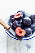 Plums - Whole and sliced in a Bowl, on a white rustic background