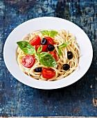 Pasta mit Tomaten, Basilikum und Oliven auf blauem Holzuntergrund