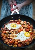 Spiegeleier, Champignons, Tomaten und Chorizobrät in einer Pfanne