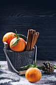 Wooden bucket with tangerines and cinnamon sticks over wooden background with snow and cone