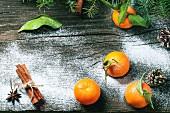 Stillleben mit Tangerinen, Zapfen und Gewürzen auf Holzuntergrund mit Schnee