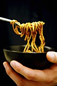 Person eating noodles out of a black ceramic bowl using a fork, black background.