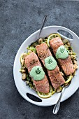 A plate white butter beans topped with oven baked salmon slices