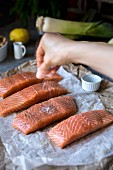 A woman is seasoning fresh salmon with salt and pepper