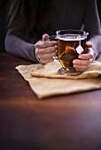 Frau mit einer Tasse heißen Tee auf Leinenserviette am Tisch