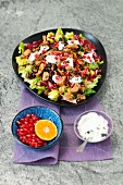 Salad with chicken, nuts, dried cranberries, pomegranate and yogurt