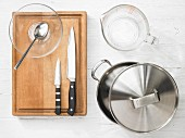 Various kitchen utensils: pot, measuring cup, knives, glass bowl, spoon