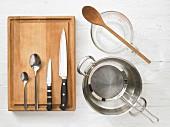 Verschiedene Küchenutensilien: Topf, Sieb, Messbecher, Löffel, Messer