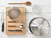 Various kitchen utensils: pot, measuring cup, sieve, knives, spoon