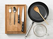 Various kitchen utensils: pan, measuring cup, pastry brush, spoon, knives