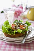 Salmon sandwich with egg, letuce, red onion, dill and a glass of white wine