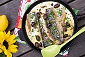 Fried mackerel with cream sauce, black olives and lemon