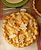 Homemade apple pie with pastry elm and maple leaves