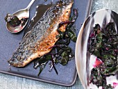 Fried mackerel fillets with red wine sauce on roasted beetroot leaves