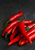 Whole fresh birds eye chillies on dark slate background