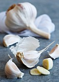 Cut up clove of purple stripe garlic with unpeeled cloves lying on a blue-grey sheet metal